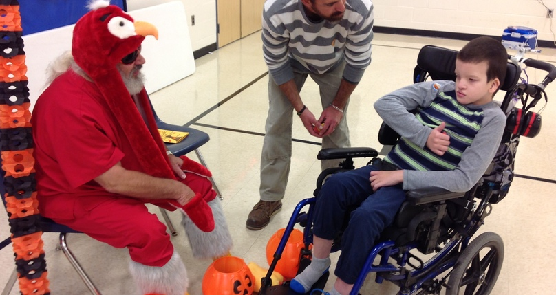 Student in wheelchair being entertained by a bird costume