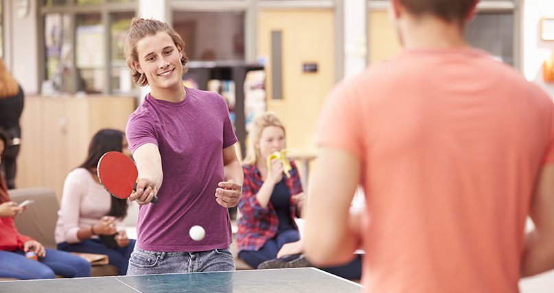 teens playing and watching ping pong