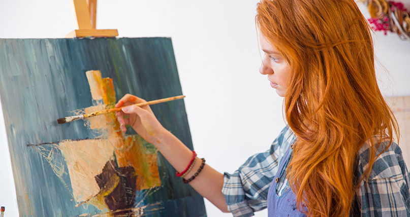 teen girl standing at an easel painting a boat