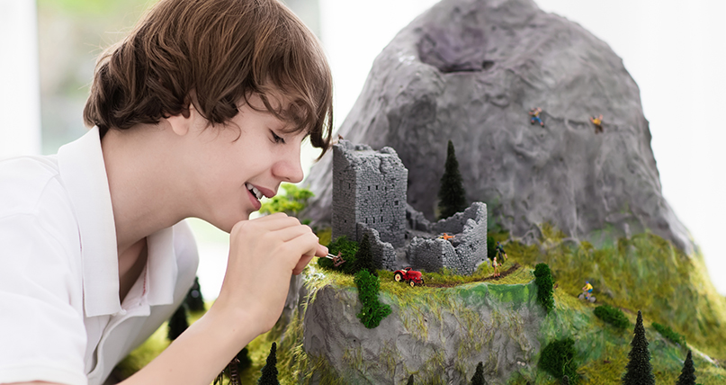 teen boy working on a class project of home made mountain