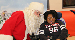 student in wheelchair posing and smiling with santa