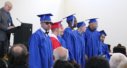 graduates stand in front of audience